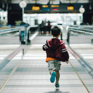 A child runs down a moving walkway in an airport