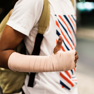A man with his arm wrapped in medical bandages gives a thumbs up expression