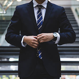 A man in a business suit adjusts his blazer buttons.
